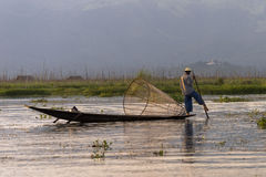 Fisherman on the Inle lake in Myanmar. A leg rowing fisherman on Inle Lake in Shan State in Myanmar (Burma).This unique style of rowing evolved because the Stock Photo