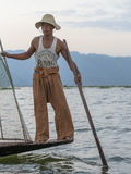 Fisherman on the Inle lake in Myanmar. A leg rowing fisherman on Inle Lake in Shan State in Myanmar (Burma).This unique style of rowing evolved because the Stock Image