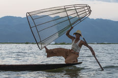 Fisherman on the Inle lake in Myanmar. A leg rowing fisherman on Inle Lake in Shan State in Myanmar (Burma).This unique style of rowing evolved because the Stock Photos
