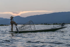Fisherman on the Inle lake in Myanmar. A leg rowing fisherman on Inle Lake in Shan State in Myanmar Burma. This unique style of rowing evolved because the Royalty Free Stock Image