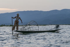Fisherman on the Inle lake in Myanmar. A leg rowing fisherman on Inle Lake in Shan State in Myanmar Burma. This unique style of rowing evolved because the Royalty Free Stock Photo
