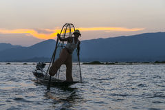 Fisherman on the Inle lake in Myanmar. Time of Sunset. A leg rowing fisherman on Inle Lake in Shan State in Myanmar (Burma).This unique style of rowing evolved Royalty Free Stock Photography