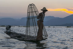 Fisherman on the Inle lake in Myanmar. Time of Sunset. A leg rowing fisherman on Inle Lake in Shan State in Myanmar (Burma).This unique style of rowing evolved Royalty Free Stock Photos