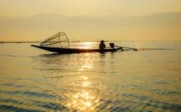Fisherman on Inle Lake, Shan, Myanmar. Fisherman on traditional teak boat  on Inle Lake in the sunset, Shan, Myanmar. Fishermen in Myanmar have a cone-shaped net Stock Photo
