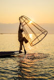 Fisherman on Inle Lake, Shane, Myanmar. Fisherman is pressing the net to catch fish on Inle Lake in the sunset, Shan, Myanmar. Fishermen in Myanmar have a Royalty Free Stock Photography