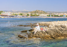 Fisherman on the island near the coast .Faliraki. Rhodes Stock Photos