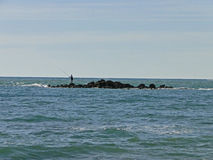 Fisherman on the island in the sea. Person fishing with a rod in a very small island in the middle of the sea Royalty Free Stock Photography