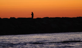 Fisherman on Jetty. Silhouette of fisherman on jetty Royalty Free Stock Image