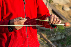 Fisherman knits fishing nets. Selective focus, copy space Royalty Free Stock Photography