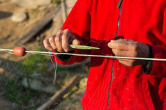 Fisherman knits fishing nets. Selective focus, copy space Stock Photo