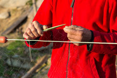 Fisherman knits fishing nets. Selective focus, copy space Royalty Free Stock Photo