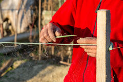 Fisherman knits fishing nets. Selective focus, copy space Royalty Free Stock Image