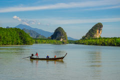 Fisherman in krabi town. A Traditional fisher boat in the krabi river with a nice mountain view Royalty Free Stock Photography