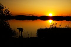 Fisherman at the lake. Man fishing in the sunset Stock Photos