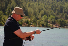 Fisherman on the lake. Adult fisherman with rod on the lake Royalty Free Stock Images