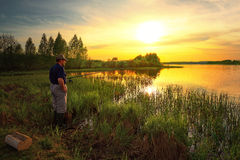 Fisherman on the lake on the background of colorful sunset Stock Image
