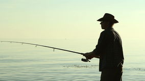 Fisherman on the lake in a cowboy hat. stock video footage