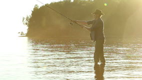 Fisherman on the lake in a cowboy hat. stock video