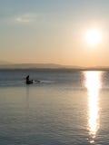 Fisherman on the Lake at Dusk Stock Images
