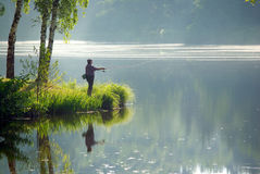 Fisherman at lake. Man fishing at misty lake in early morning Stock Images