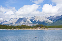 Fisherman on Lake in Mountains. Fisherman on Upper Kananaskis Lake in the Canadian Rocky Mountains Stock Photo