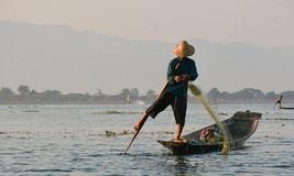 Fisherman on a lake in Myanmar. A fisherman stands on his boat in a lake in Myanmar. The location is Inle Lake, a famous tourist destination in Myanmar, known Royalty Free Stock Photos