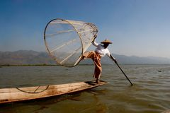 Fisherman on a lake in Myanmar. A fisherman stands on his boat in a lake in Myanmar. The location is Inle Lake, a famous tourist destination in Myanmar, known Stock Photos
