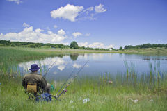 Fisherman on the lake shore. Fisherman sitting on the lake shore Royalty Free Stock Photography