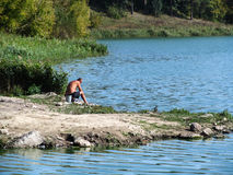 Fisherman on the lake shore. Fat man fishing on the lake in the forest Stock Photos