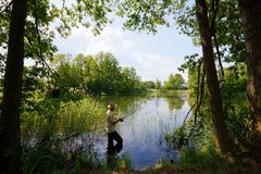Fisherman. In the lake during sunny day Stock Photo
