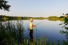 Fisherman. In the lake during sunny day Royalty Free Stock Image