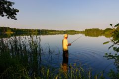 Fisherman. In the lake during sunny day Stock Image
