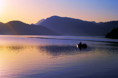 Fisherman On Lake At Sunrise Stock Photography