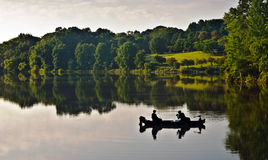 Fisherman on the lake at sunrise. A pair of fisherman in a boat on a quiet lake at sunrise, at Centennial Lake in Columbia Maryland royalty free stock photos