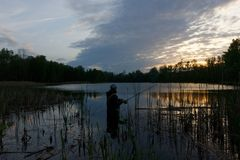 Fisherman. At the lake during sunset Stock Photography