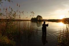 Fisherman. At the lake during sunset Stock Photos