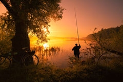 Fisherman on the lake at sunset. Silhouette of fisherman with fishing rod on the lake at sunset Royalty Free Stock Image