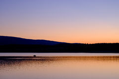 Fisherman on Lake at sunset royalty free stock photography