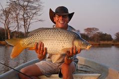 Fisherman with large carp. Closeup of smiling young fisherman in boat holding large common carp fish, river in background Royalty Free Stock Photography