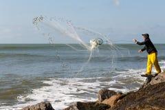 Fisherman. Launching his fishing net stock photos