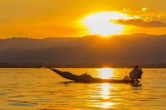 Fisherman with Leg rowing during Sunset,  inle lake in Myanmar ( Stock Photos