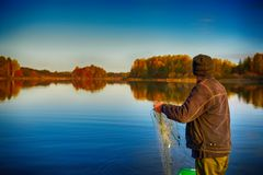 Fisherman lifts fishing net on the boat Royalty Free Stock Images