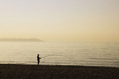 Fisherman. Lonely Fisherman on the Beach at Sunrise Time.  Mediterranean Sea, Greece Royalty Free Stock Images