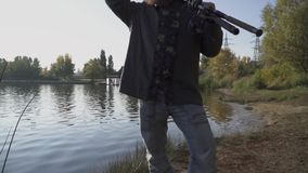 Fisherman with long beard stends on the river bank with fishing rods. The man looks into the distance, covering his eyes. With his hand from the sun. The man is stock footage