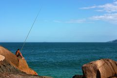 Fisherman with a long fishing rod in Brazil. JOAQUINA BEACH, FLORIANOPOLIS, SANTA CATARINA, BRAZIL - MARCH 22, 2009: An isolated man fishing over the rocks stock images