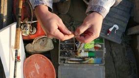 Fisherman making a fishing knot. stock video
