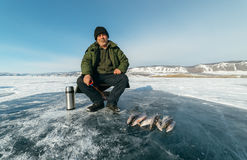 Fisherman is a man in winter fishing. Royalty Free Stock Photography