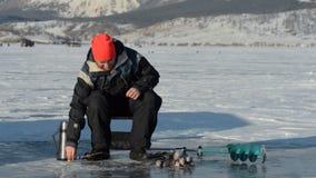 Fisherman is a man in winter fishing. stock video