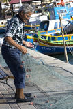 Fisherman at Marsaxlokk harbour. An adult fisherman is fixing his nets after a morning of fishing - Articles about fisherman, Malta, Europe, Culture and Stock Images
