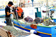 Fisherman, Marsaxlokk, Malta. A fisherman checking his nets on the quayside at marsaxlokk, Malta Royalty Free Stock Photos